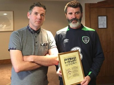 Roy Keane holding a sign posing for the camera