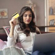 A girl sitting on a sofa holding laptop