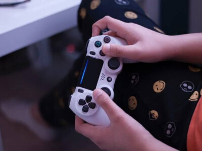 A person holding video game remote