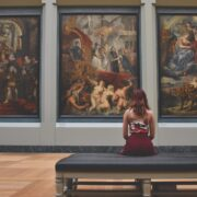 A girl sitting on bunch in front of paints